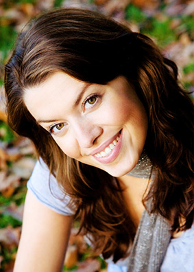 Smiling girl wearing Lumineers, a kind of veneers for teeth, from a Bloomington dentist.