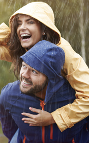 Couple in the rain have glowing smiles thanks to aesthetic dentistry near Handy and Ellettsville.